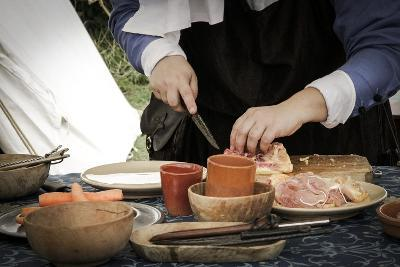 Historical Reenactment: Woman Preparing Meat for Lunch in Military Camp, 14th Century