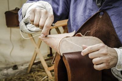 Historical Reenactment: Shoemaker Sewing Sole of Pair of Shoes, End of 18th Century