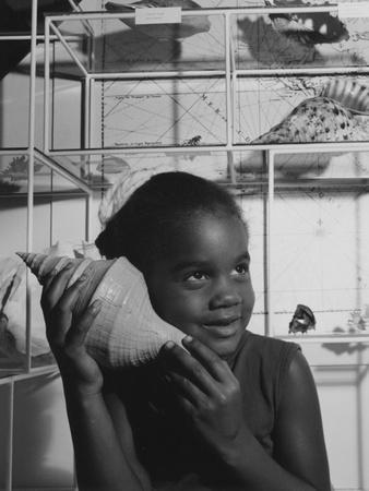 A Young Girl Holding a Large Seashell to Her Ear