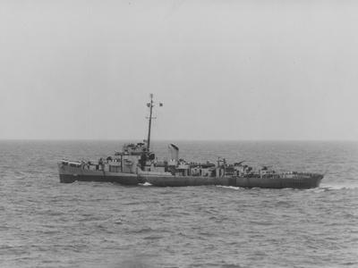 The USS Chatelain at Sea with the Crew Gathered on the Bow