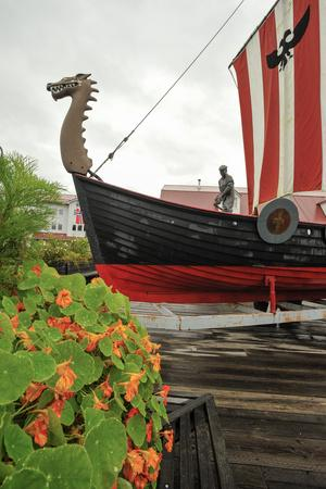 A Red and Black Viking Ship and a Statue of a Fisherman in Petersburg, Alaska
