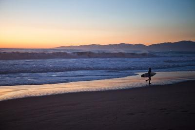El Porto Beach, Los Angeles, California, USA: A Surfer Exits the Waves at Dusk