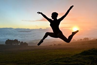A Ballerina Dances Beneath a Cloud-Filled Sky