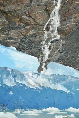 A Waterfall Cascades Down a Cliff Behind an Electric Blue Iceberg from Dawes Glacier