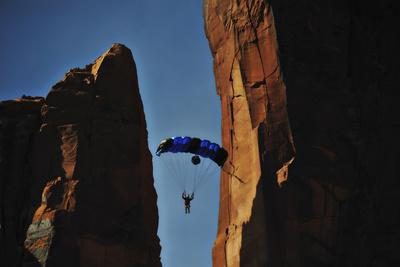 A Man Parachutes after Base Jumping Off a Desert Spire from Fisher Towers