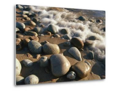 Water Washes up on Smooth Stones Lining a Beach