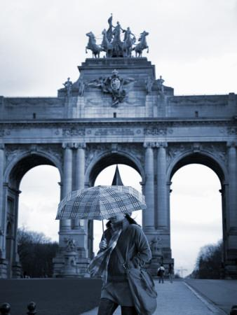 Belgium, Brussels; a Girl Walking with an Umbrella in Front of the Arc Du Triomphe