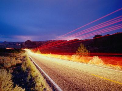 Vehicle Lights and Lightning Illuminating Road, Arches National Park, Utah, USA