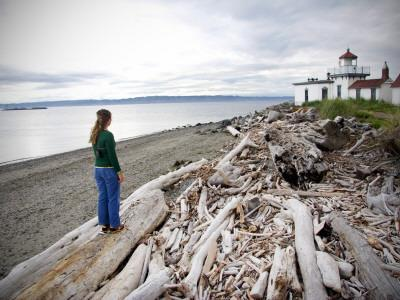 Woman Standing on Driftwood and Looking Towards Discovery Park Lighthouse