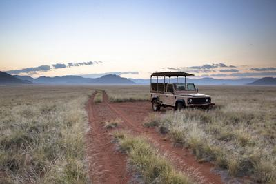 Land Rover Game Vehicle Parked by Sand Road at Sunrise