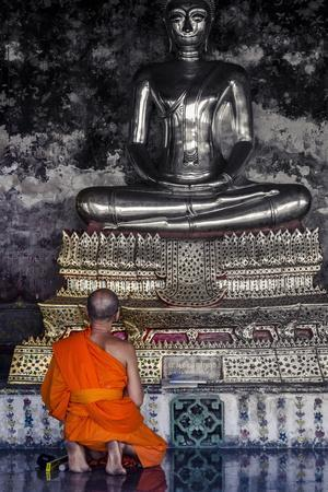 A Monk Prays in Front of a Golden Buddha, Wat Suthat, Bangkok, Thailand, Southeast Asia, Asia