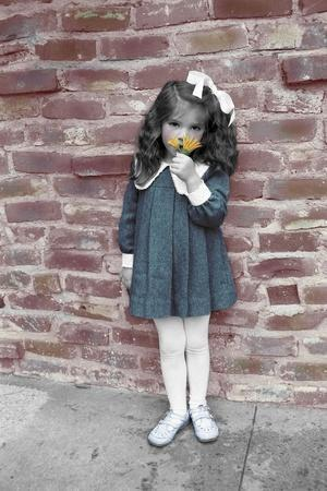 Young Girl Standing in Front of a Stone Wall Smelling a Flower.