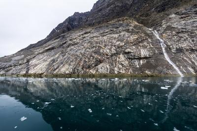 A Small Waterfall Running Down a Cliff into the Darks Waters of a Fiord