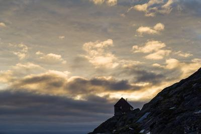 The Silhouette of a Cottage Perched on a Rocky Outcrop on an Arctic Island