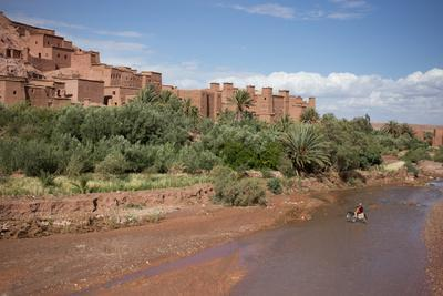 A Man on a Donkey Crossing the River in Front of Ait Benhaddou, Morocco