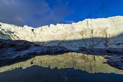 The Setting Sun Reflects the Sheer Ice Cliff of a Glacier Fracture Zone in a Pond