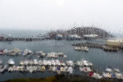 A Rain Storm Lashing a Window Overlooking a Fishing Boat Harbor