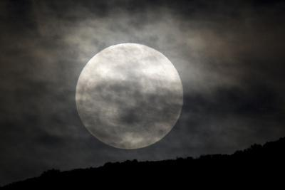 The Full Moon over a Shadowed Landscape