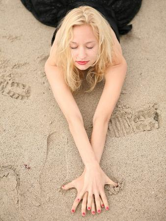 Young Woman Wearing a Black Party Dress Stretching Her Arms on the Beach