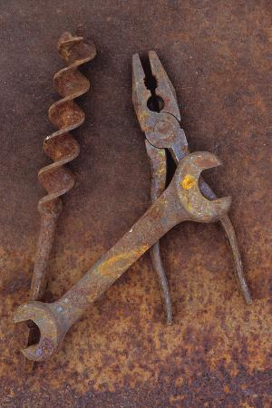 Rusty Old Double-headed Spanner Lying Next To Large Drill Bit And Rusty Pliers On Rusty Metal Sheet