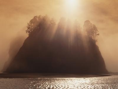Sun Beams Breaking through Fog over Sea Stack