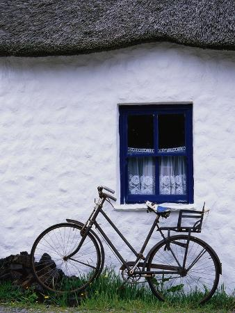Bicycle Leaning Against a Thatch-Roof Cottage