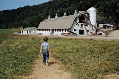 Boy Walking Towards a Barn