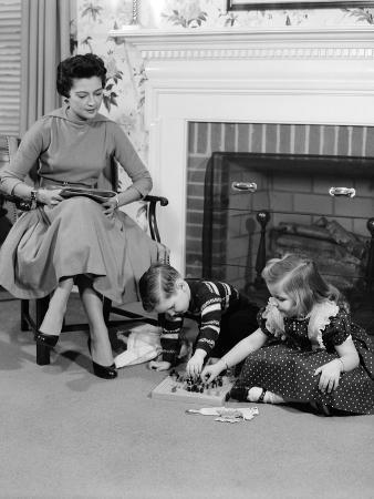 1950s Mother Watching Son Daughter Playing Game in Front of Fireplace