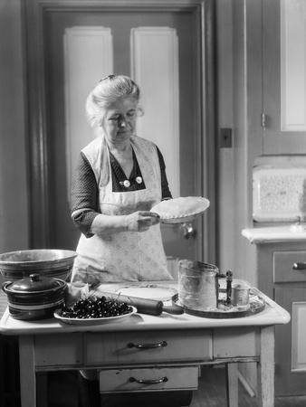 1920s-1930s Senior Woman Grandmother Wearing Apron Crimping Crust Making a Cherry Pie in Kitchen