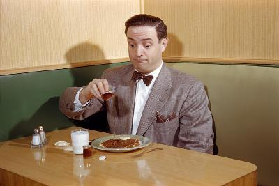 Businessman Pouring Syrup on Pancakes