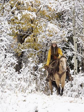 Cowgirl Riding in Autumn Aspens with a Fresh Snowfall