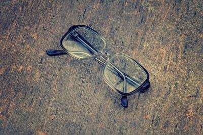 Eyeglasses Laying on a Grungy Wooden Background with Retro Filter Effect
