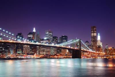 New York City Brooklyn Bridge and Manhattan Skyline with Skyscrapers over Hudson River Illuminated