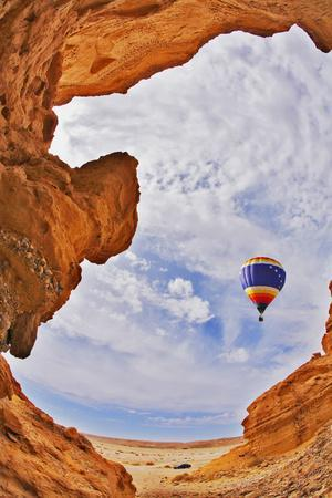 The Balloon Flies above a Picturesque Slot-Hole Canyon in Desert
