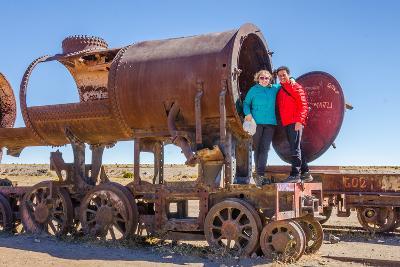 Couple of Tourists Visiting Cementerio De Trenes (Train Cemetery), Salar De Uyuni, Bolivia