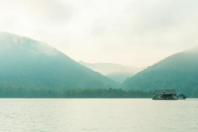 Hut on Water in Morning Time with Mountain and Fog