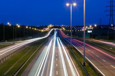 Highway Traffic at the Evening. Cars Lights in Motion on the Streets. Transport, Transportation Ind