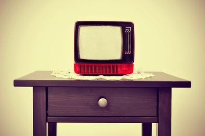 An Ancient Red Television on a Table with a Retro Effect