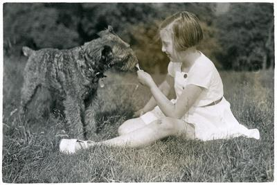 Girl Offering Her Dog a Lollipop