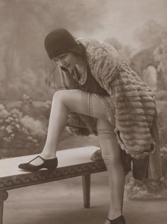 Young Woman Wearing a Fur Coat Cloche Hat and T-Bar Shoes Lifts Her Leg Up