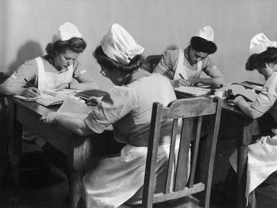 Four Young British Student Nurses Making Notes Together from Medical Textbooks