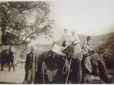 Two Well-Dressed English Women Riding on an Elephant, with the Aid of Young Indian Men