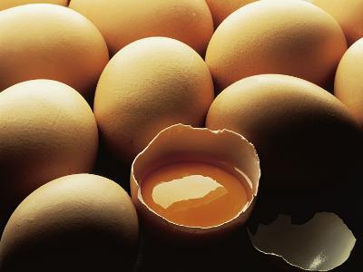 Close-Up of a Broken Egg over a Heap of Eggs