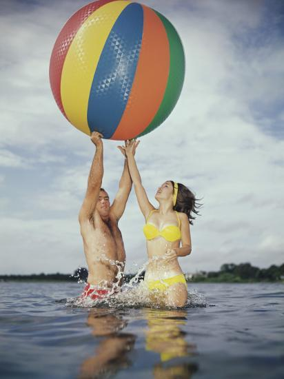Jumping In Water Reaching For Large Beach Ball