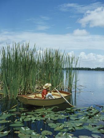 Retro Boy Pole Fishing in Lake Inside Canoe