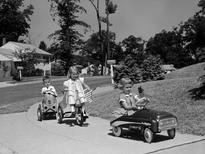 Boy and Two Girls on Suburban Sidewalk, Riding Tricycle and Toy Cars