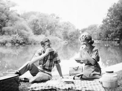 Couple Seated on Checkered Tablecloth With Picnic Basket and Cooler, Eating Sandwiches By Lake