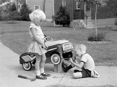 Children on Suburban Sidewalk, Boy Playing As Mechanic, Oiling Toy Pedal Car