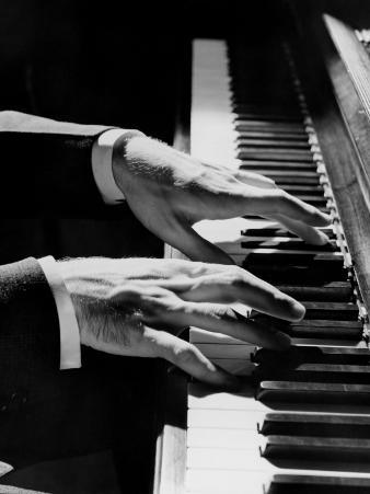 Man's Hands Playing Piano in Dim Lighting