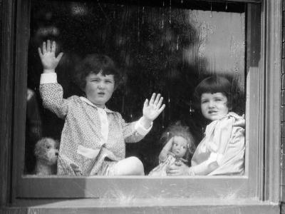 Two Frowning Girls With Dolls Looking Out Large Window at Rain Drops